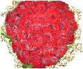 Красные розы в виде сердца с гипсофилой и зеленью
