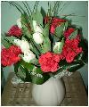 Яркий контрастный букет из 9 белых тюльпанов и 7 красных гвоздик с берграсом, зеленью в натуральной упаковке