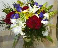Яркий букет из цветков лилий, красных роз, орнитогалума, ирисов, желтой кустовой хризантемы с зеленью в натуральной упаковке.